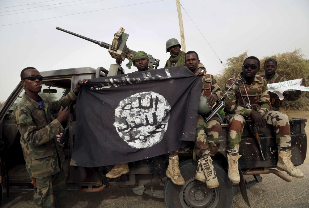 Nigerien soldiers hold up a Boko Haram flag that they had seized in the recently retaken town of Damasak, Nigeria